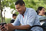 Summer. A Man Sitting On A Bench Using A Digital Tablet.