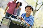 A Boy Riding An Old Fashioned Toy Peddle Car.
