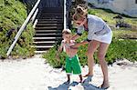 Mother applying sun cream to toddler at beach