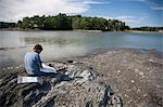 Mature man sitting on rocks looking at maps, Bath, Maine, USA