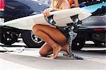 Woman kneeling with surfboard, Hermosa Beach, California, USA