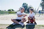 Man giving grandson basketball pep talk