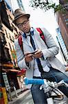 Young man on bike using smartphone