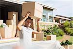 Man holding cardboard box overhead near moving van in driveway