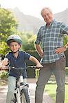 Older man teaching grandson to ride bicycle