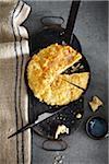 Cheesy Bannock bread in baking pan on grey background, studio shot