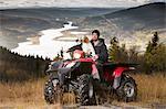 Man with dog on four-wheeler vehicle