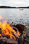 Bonfire at dusk by lake