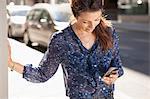 Businesswoman using mobile phone on street