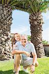 Older man and granddaughter smiling in backyard