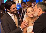 Father kissing bride's cheek at wedding reception