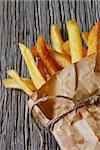 Fried potato in a kraft bag on an old wooden board.