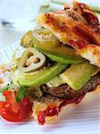 A mediterranean pork burger with avocado slices and foccacia bread