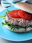 A tuna burger in a sesame seed bun