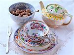 A stack of antique crockery tea pot sugar bowl