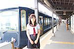 Woman wearing school uniform on railway platform at train station