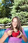Girl eating by pool