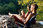 Young couple relaxing on rock ledge, Hamburg, Pennsylvania, USA