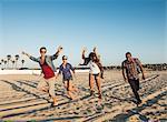 Friends running on Mission Beach, San Diego, California, USA