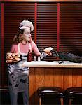 1950s WOMAN WEARING CHEF'S HAT APRON HOLDING TRAY OF HAMBURGERS FEEDING HAMBURGER TO IGUANA ON COUNTERTOP