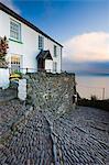 Winding cobbled lane and whitewashed cottage in Clovelly, Devon, England, United Kingdom, Europe