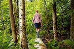 A woman in wellingtons walking along a fallen tree trunk, in woodland.