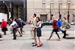 Couple standing on sidewalk on busy, city street, Toronto, Ontario, Canada
