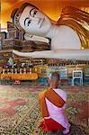 Nun in front of reclining Buddha statue, Shwethalyaung, Bago (Pegu), Myanmar (Burma), Asia