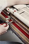 A piano repairman using pliers to fix a piano