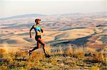 Young woman running on hill, Bainbridge Island, Washington State, USA