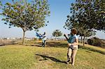Senior couple running in park with kite
