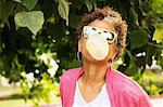 Senior woman blowing bubble gum