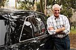 Senior man standing against black vehicle