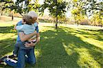 Grandfather kneeling on grass hugging grandson