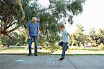 Boy on hopscotch, grandfather watching