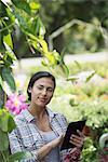 A woman in an organic nursery greenhouse, using a digital tablet.
