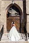 Backview of bride in wedding gown, standing in front of church door on Wedding Day, Canada