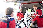 Paramedics lifting woman on stretcher into ambulance