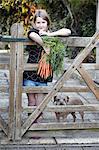 Girl in garden holding bunch of carrots