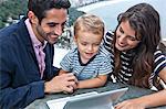 Young family looking at laptop, Casa Alto Vidigal, Rio De Janeiro, Brazil