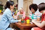 Flatmates sharing plans around kitchen table