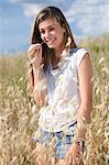 Teenage girl in field biting grass, Tuscany, Italy