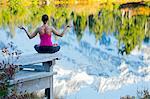Woman meditating by lake, Bellingham, Washington, USA