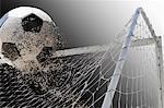 Studio shot of football powering through goal netting