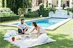 Couple enjoying picnic by pool
