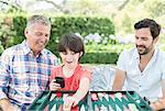 Men playing backgammon outdoors