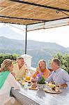 Senior couples enjoying breakfast on balcony overlooking mountains