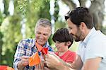 Multi-generation men making origami outdoors