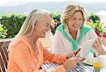 Senior women using digital tablet at patio table