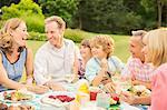 Multi-generation family enjoying lunch in backyard
